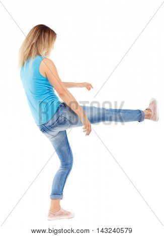 back view of woman funny fights waving his arms and legs. Rear view people collection. backside view of person.  Isolated over white background. The blonde in a blue shirt and jeans, raised her leg.