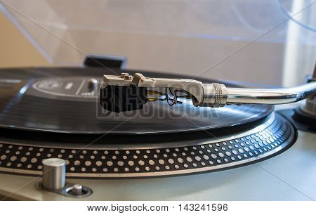 Close up of a turntable needle head playing music from an lp. (shallow focus).