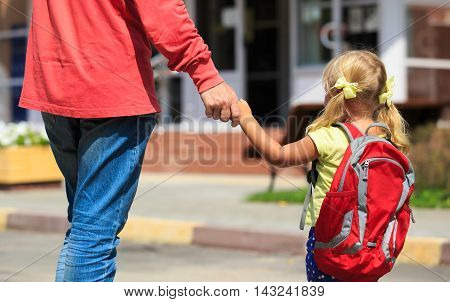 father walking little daughter to school or daycare, back to school