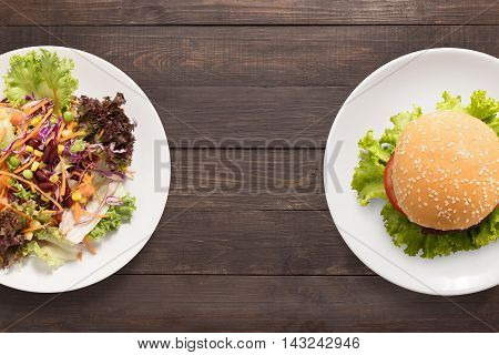 Fresh Salad And Burger On The Wooden Background. Contrasting Food