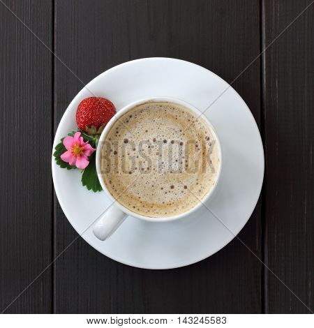 frothy coffee with decoration of berries flower and leaf strawberries on a dark wooden background top view / coffee break with strawberry aroma