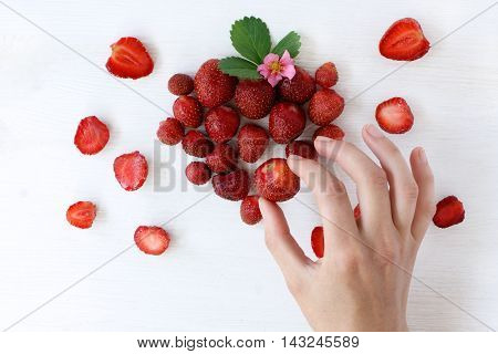 man's hand puts strawberry background berries top view / decoration in shades of strawberry