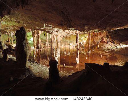 Illuminated subterranean lake in a dripstone cave.
