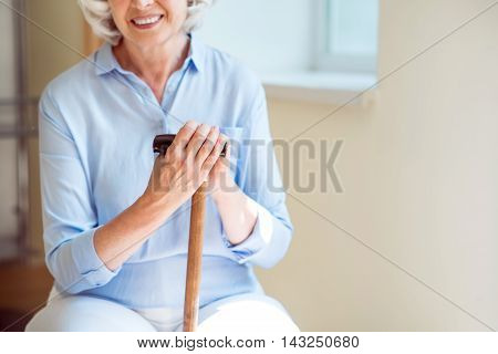 Smile in spite of all. Cropped picture of smiling and content senior woman holding crutch