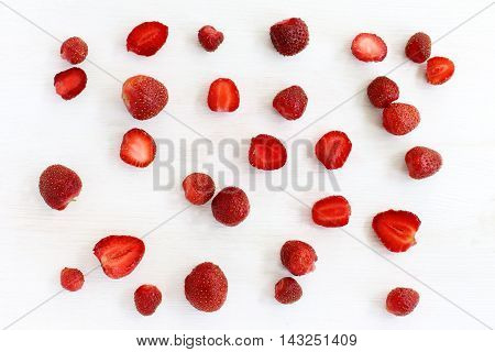 flat lay plurality of of red strawberries on a wooden surface top view / strawberry background