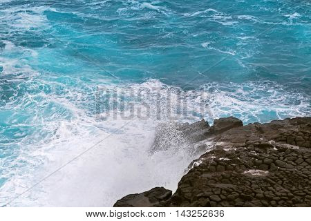 Deep blue sea water splashing volcanic rock at blowholes, rock tunnels, at Cape Bridgewater in Victoria, Australia