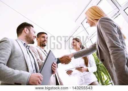 Handshake between two business executives.Image of four successful business partners working at meeting in office.They are working on a new project.