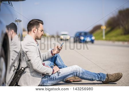 A young man with a silver car that broke down on the road.He is waiting for the technician to arrive.