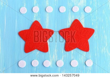 Cut red and white felt details to create Christmas star decor. Fun craft technique for children. Step-by-step. Christmas star tutorial. Blue background. Top view. Closeup