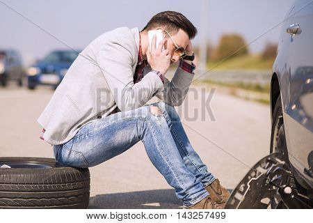 A young man with a silver car that broke down on the road.He is calling for the technician to arrive.