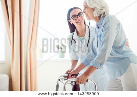 Professional one. Cropped image of young doctor helping senior woman with walking frame