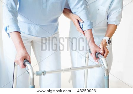 Volunteer. Cropped image of professional doctor helping senior woman with walking frame