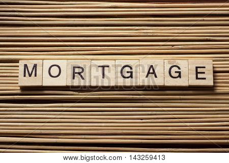 MORTGAGE word written on wood block at wooden background.