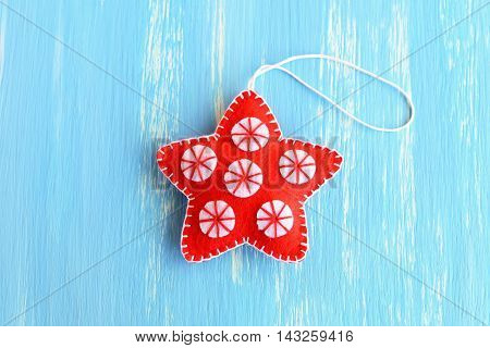 Red Christmas star ornament isolated on a blue wooden background. Handmade felt star with white circles. Christmas home decor. Winter kids crafts. Closeup. Top view