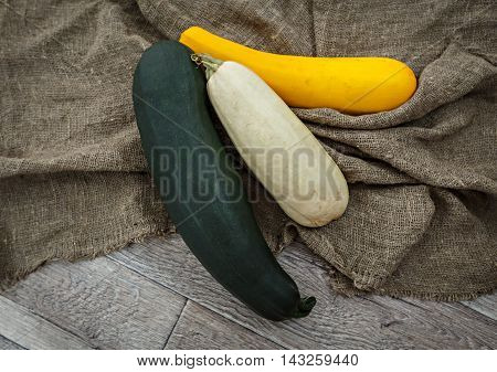 Fresh zucchini or marrow squash or courgette on rustic burlap background. Vegetables in different shapes and colors concept of diversity horizontal top view
