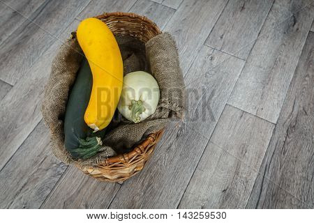Fresh zucchini or marrow squash or courgette in basket on burlap against wooden background. Vegetables in different shapes and colors concept of diversity top view with copy space