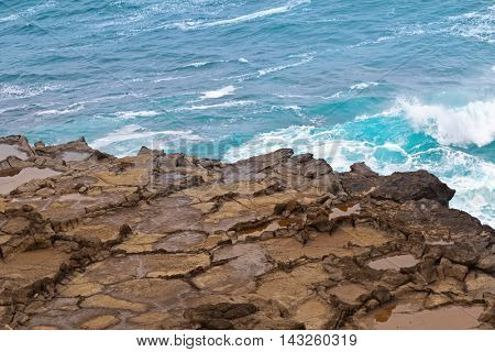 Deep blue sea water splashing volcanic rock at blowholes at Cape Bridgewater in Victoria, Australia