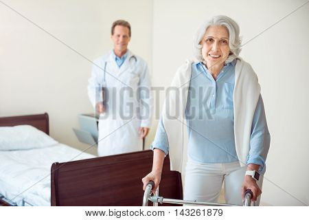 Rehabilitation. Smiling old woman with walking frame and her doctor in background