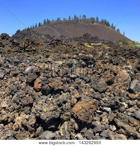 Lava Butte in Central Oregon as seen through the lava field on a sunny day.
