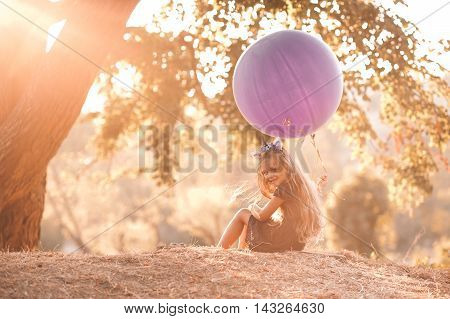 Cute kid girl 4-5 year old holding big purple balloon sitting under tree in sun light. Looking at camera. Wearing summer dress. Posing outdoors. Selective focus.