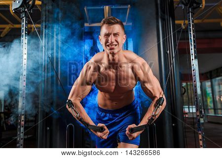 Man at the gym. Man doing exercises on the simulator. Sport, power, dumbbells, tension, exercise - the concept of a healthy lifestyle.