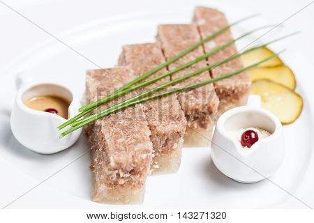 jellied meat dish on white background with sauce