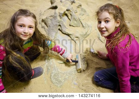 Two girls dig together in dry sand bones of dinosaur in sand