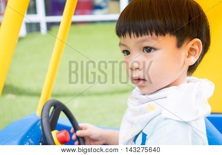 Asian child is riding on a colorful toy car