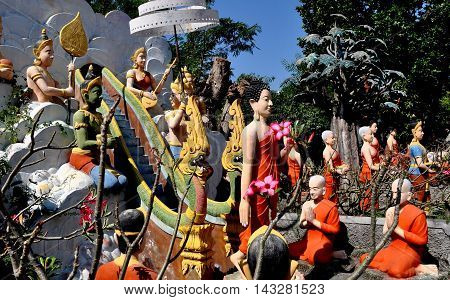Bang Saen Thailand - January 9 2014: Colourful statues of orange-robed monks deities and people stand in the gardens at Wat Saen Suk