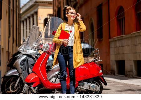 Young female student standing with books and backpack near red scooter on the street in Bologna city in Italy