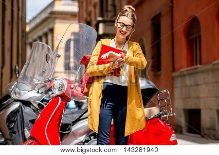 Young female student with books and backpack looking at the smartwatch standing near red scooter on the street in Bologna city in Italy