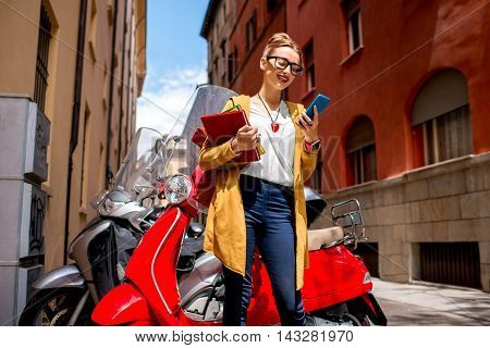 Young female student with books and backpack using smartphone standing near red scooter on the street in Bologna city in Italy