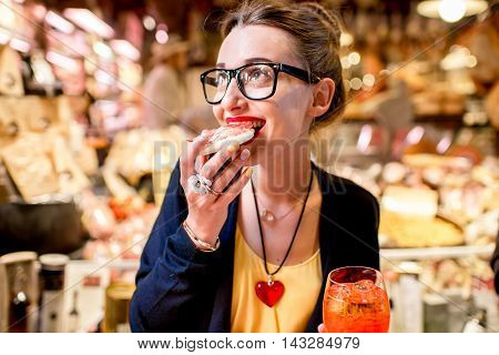 Young woman eating bread with prosciutto in front of food showcase in Bologna city.