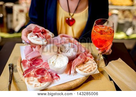 Traditional italian appetizer with proscioutto, mortadella sausage, cheese, bread and aperol spritz drink on the wooden board.