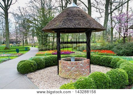Lisse, Netherlands - April 4, 2016: Old well in the spring flower garden and Keukenhof park view
