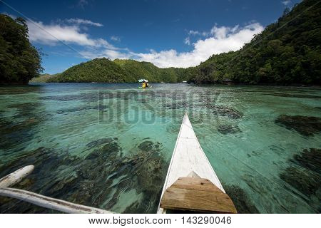 A canoe paddles over clear tropical water