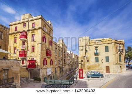 Malta, Valletta - Red telephone box and traditional red balconies at Valletta with blue sky
