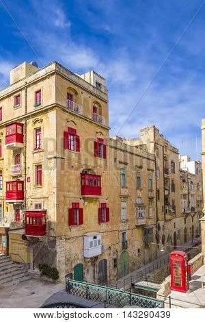 Streetview of Valletta, Malta with red balconies and windows