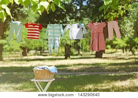 Wicker basket and baby laundry hanging on clothesline