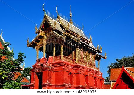 Lamphun Thailand - December 28 2012: Repository Library built on a red sand stone base with gilded roof wooden dragons and chofah ornaments at Wat Phra That Haripunchai Maha Viham *