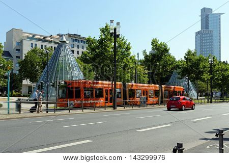 FRANKFURT AM MAIN GERMANY - AUGUST 7 2015: An electric tram near the Festhalle and Trade Fair tube station and the Westend Tower in the background.