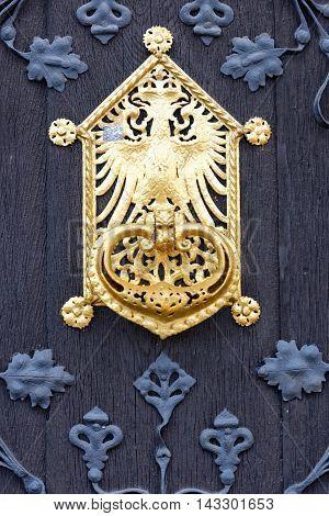 Close up of a black traditional German doorway with golden doorknob accents.