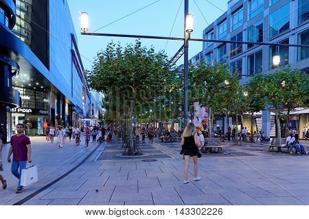 FRANKFURT AM MAIN GERMANY - AUGUST 7 2015: People walk along the Zeil at sun set. Since the 19th century it is of the most famous and busiest shopping street in Germany.
