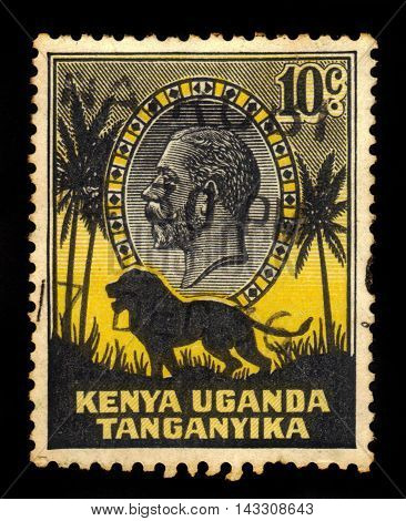 KENYA, UGANDA AND TANGANYIKA - CIRCA 1935: a stamp printed in East Africa showing image of a lion and palm trees against the portrait of King George V, circa 1935.