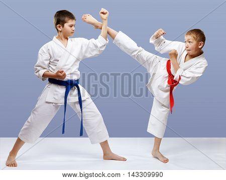 Kick leg and block are doing sportsmen in karategi