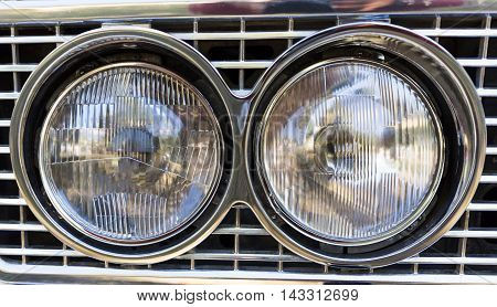 Detail of an attique car at a retro car parade. Two headlights. Headlamps.