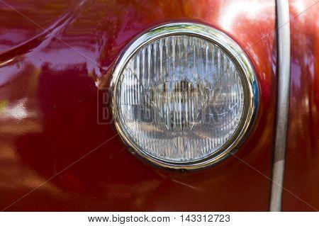 Detail of an attique car at a retro car parade. Headlights. Red headlamp.