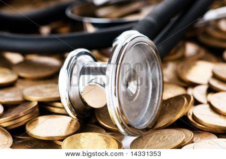 Conceito de cuidados de saúde caro com moedas e estetoscópio