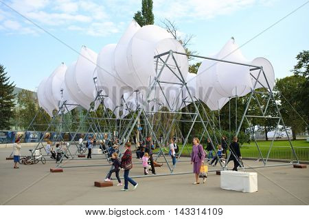 MOSCOW - SEP 22, 2015: People on swing with sail in summer park of VDNH