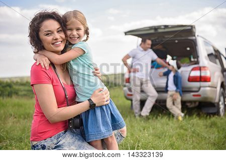 Fun moments diring trip. Mother and daughter having fun together and hugging each other with father and brother in background
